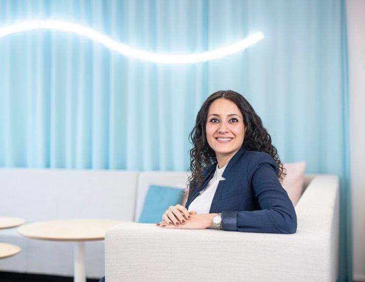 Fahimeh Farhadian sitter i en vit soffa med en blå vägg och ett vågformat lysrör i bakgrunden.