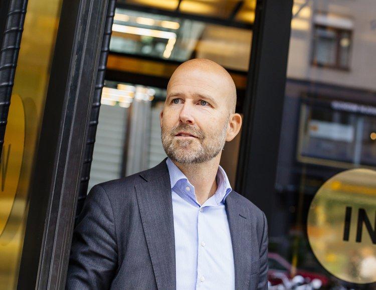 Joakim Nordenstam klädd i grå kostym med blårandig skjorta står framför DNBs  entré, utsmyckad av gulddetaljer.