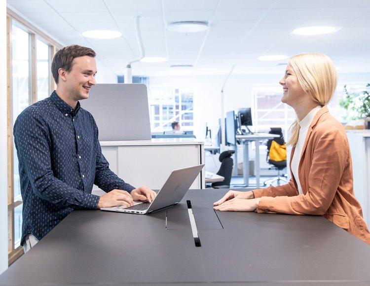 Rebecca sitter vid ett bord på JM:s kontor mittemot en kollega.