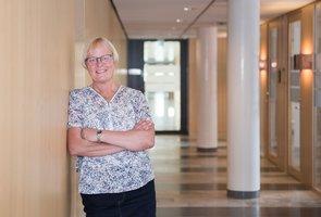 Eva Lindberg, personalchef Skellefteå Kraft står lutandes mot en vägg i de luftiga lokalerna på huvudkontoret.