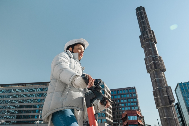 Woman in a helmet and white jacket standing on a Voi in Stockholm