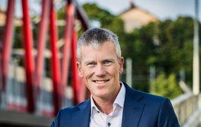 Gustaf Meland står utomhus, iklädd kostym, på en gångbro med en röd bro  och grönskande träd i bakgrunden.