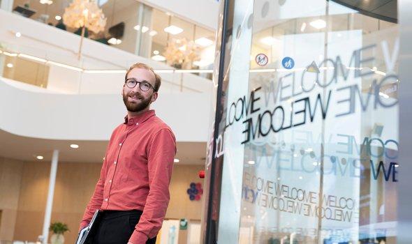 Philip Blomström står i Essitys ljusa lokaler med inomhusbalkonger i bakgrunden.