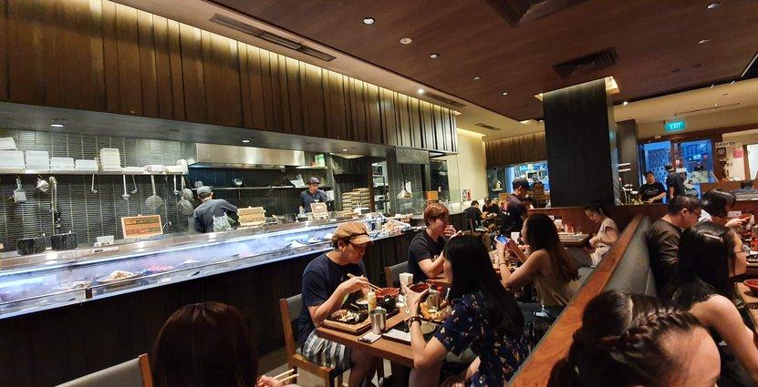 Folk går ut och äter i Singapore men sitter lite längre ifrån varandra Anders Johansson