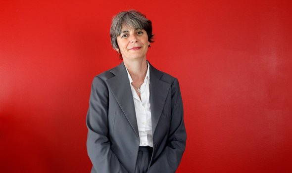 Pascale Gimenez står i grå kostym framför en röd vägg.