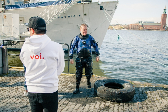 A diver on land with a car tyre found on the seabed.