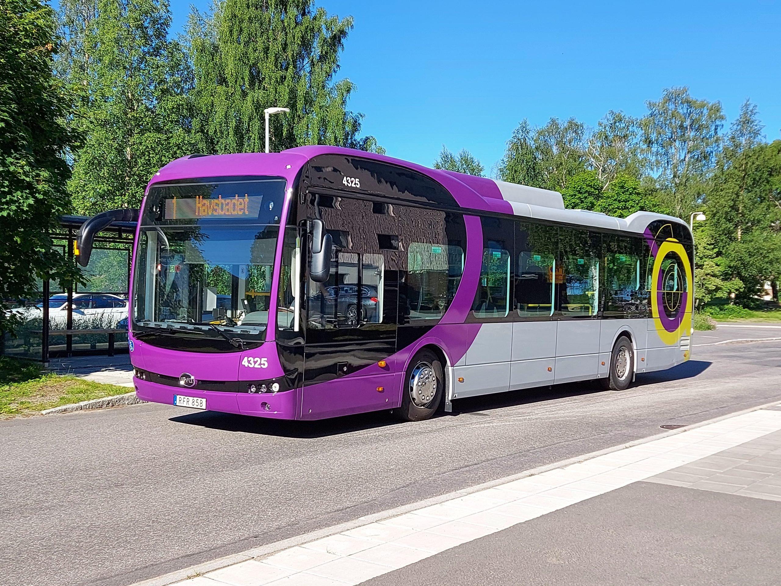 En lila och grå elbuss står på en parkering