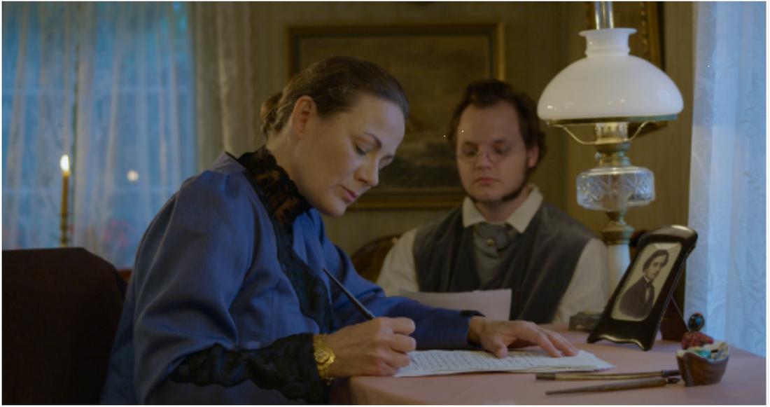 Författarinnan med maken J.G. Carlén, spelade av Camilla Hedin och Daniel Olsson.