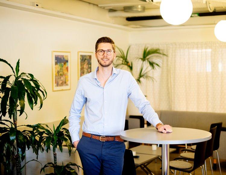 Theodor Danielson står lutad mot ett ståbord på ett kontor. Han ler mot kameran. Bakom honom står en soffgrupp.