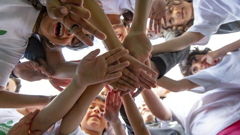 Barn står i en ring och lägger händerna över varandra i en aktiv gemenskap.