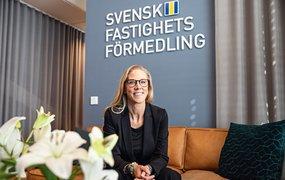 Josefin Thörnert är rekryteringschef på Svensk Fastighetsförmedling. Hon sitter framåtlutad i en congacfärgad skinnsoffa och ler mot kameran. På den blågrå väggen bakom sitter Svensk Fastighetsförmedlings logotyp. I förgrunden syns en bukett vita liljor.