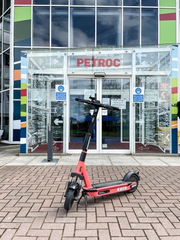 An electric scooter parked in front of the entrance to a building