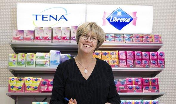 Anna-carin Elfström ståendes framför en hylla full av essitys färgglada produkter som Tena och Libress.