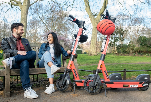 a man and a woman sitting on a bench in a park next to two red Voi scooters