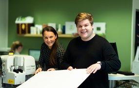 Carl Johansson visar en skogsindustribolagets produkter i form av ett stort vitt ark tillsammans med en kollega.