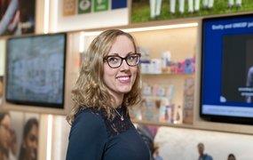 Åsa Gidsäter Roos står i Essitys lokaler med en hylla och tv-skärmar bakom sig.