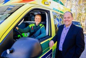 Ambulanssjuksköterskan Emelie Askelin sitter i förarsätet i en ambulans med högra handen på ratten och ler mot kameran, fönsterrutan är öppen. Utanför bilen står Uno Lundberg, vd på Falck Emergency. Han lutar ena armen mot bilens dörr och ler även han mot kameran.