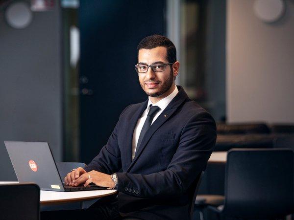 Rami Hussein sitter vid ett bord i en av CGI:s lokaler med en dator framför sig.