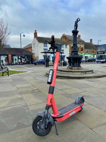 coral red voi e scooter in front of a black statue in Kettering, United Kingdom