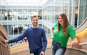 Matilda Stendahl och Stefan Liss  står i en spiraltrappa i en ljusgård. Bakom dem ser man flera kontorsvåningar. De ler mot kameran.