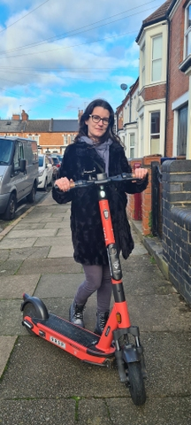 woman standing behind a Voi e-scooter in Northampton