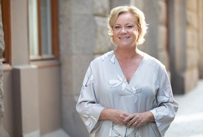 Lisa Oldmark, HR-direktör på AcadeMedia står ute på gatan i solskenet framför AcadeMedias byggnad i centrala Stockholm.