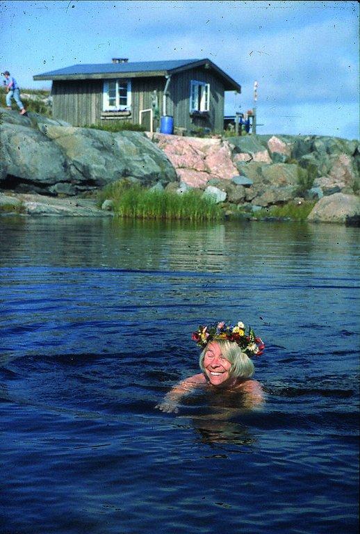 Tove simmar på Klovharun. I bakgrunden syns Tuulikki Pietilä. Foto: ©Moomin Characters™