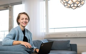 Hanna Ekberg sitter i en soffa med en dator i knät, och ett fönster i bakgrunden.