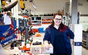 Alba Sadikovska, labbingenjör på Husqvarna Group, står i en garageliknande byggnad, vid en arbetsbänk. På bänken ligger massor av olika verktyg.