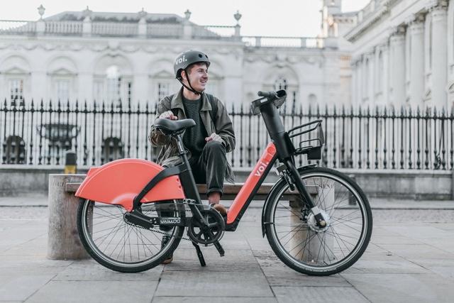 man standing behind a voi e-bike on a street
