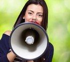 Kvinna talar i megafon.