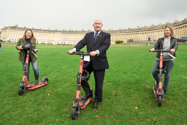 people on Voi scooters