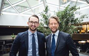 Henrik Olausson, vd, och Lukas Hernblad, rekryteringschef, står inomhus i en kontorsbyggnad. Ovanför dem syns ett stort glastak som släpper in ljus, och bakom dem ett stort träd. De ler mot kameran.