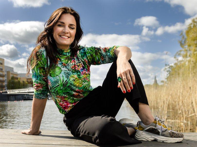 Porträttbild på Ylva Hällen som sitter på marken med blå himmel bakom