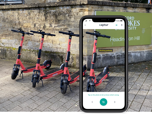 An iphone taking a photo of four Voi e-scooters lined up in a row
