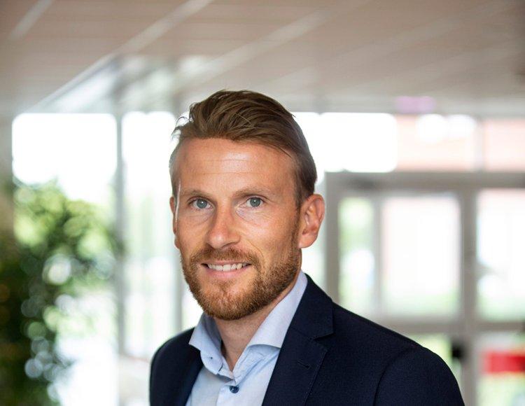Marknadsdirektör Michael Almqvist Maisor står i en ljus lokal med gröna växter och fönster bakom sig.