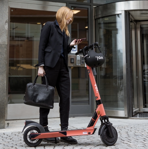 woman in a black suit standing next to a Voi e-scooter
