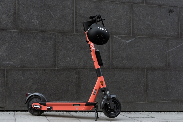 Voi e-scooter photo with helmet over the handlebars in front of a grey concrete wall