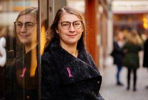 Irina Gavryukhova står utomhus lutad mot en glasvägg.