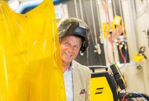 Sten Wallin, vd, i en av ESAB:s fabriker klädd i skyddshjälm och kostym.