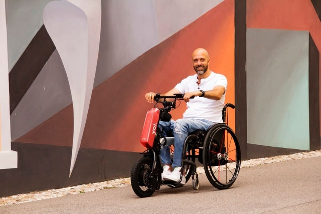 Male seated in a wheelchair using the Voi-branded Klaxon Klick device