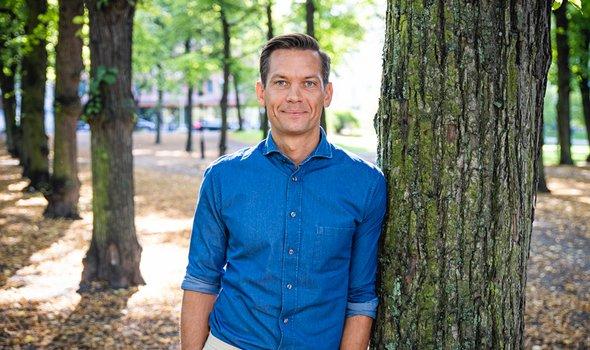 Rikard Nyhren står i blå skjorta utomhus och lutar sig mot ett träd.