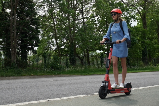 A woman with a helmet is riding an electric scooter on the road
