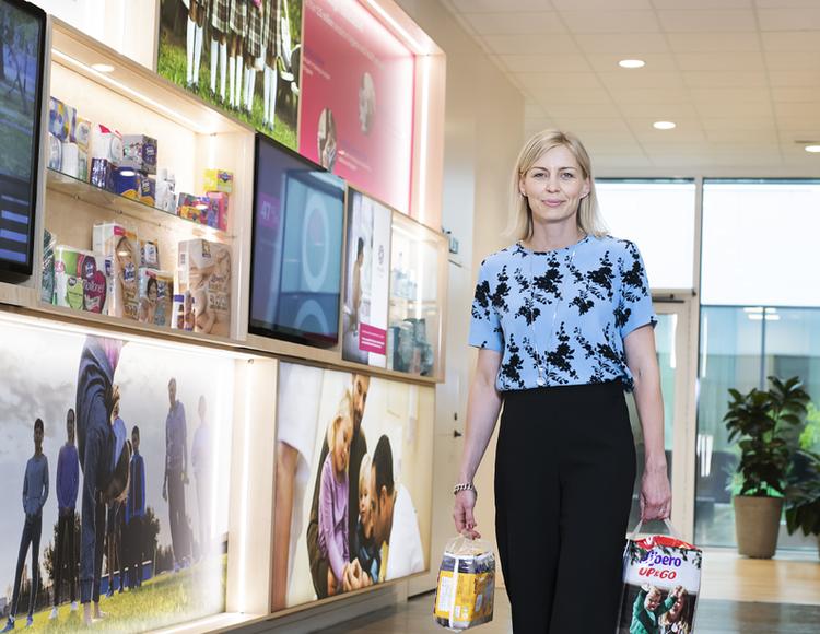 Klara Svanström ståendes på Essitys kontor. I händerna håller hon produkter som Liberos blöjor