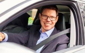 Per Tillman, Vice President Talent Management, sitter i förarsätet i en bil klädd i kostym och ljus rutig skjorta.