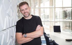 Johan Kvarnström står lutad mot en vägg med stora fönster i bakgrunden.