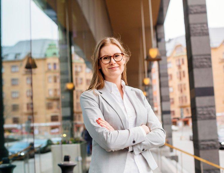Rebecka Karlsson står med armarna i kors utanför en byggnad med stora glasfönster. Hon ler och tittar in i kameran.