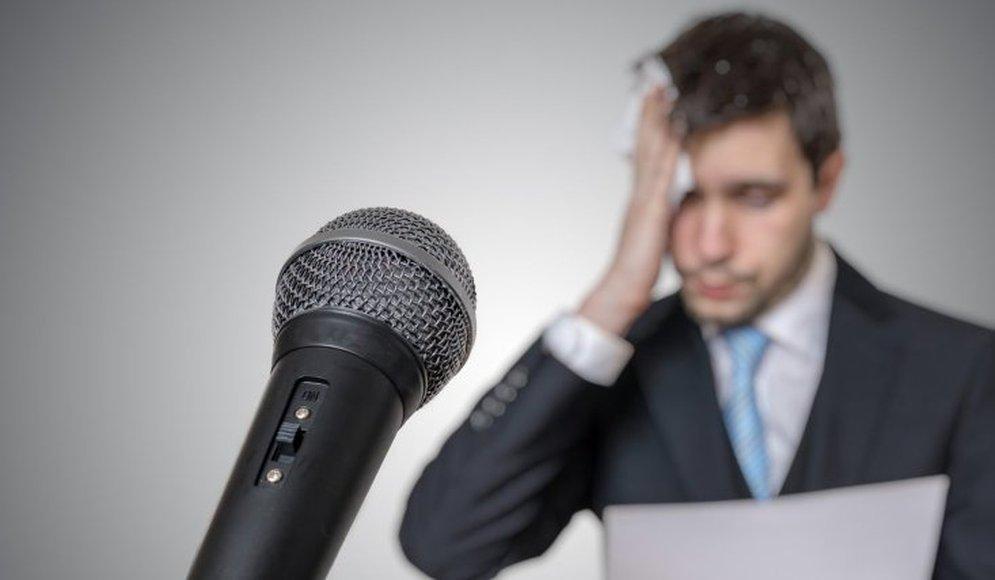 Bilden föreställer en man som torkar sig i pannan och ser besvärad ut. I framkant av bilden är en mikrofon.