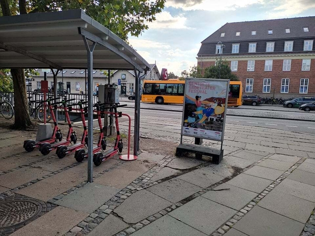 five red e-scooters parked in a parking rack outside Hellerup station in Gentofte