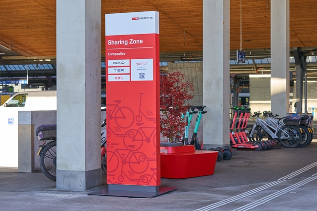 e-scooters and e-bikes parked in a shared mobility hub outside an SBB train station in Switzerland